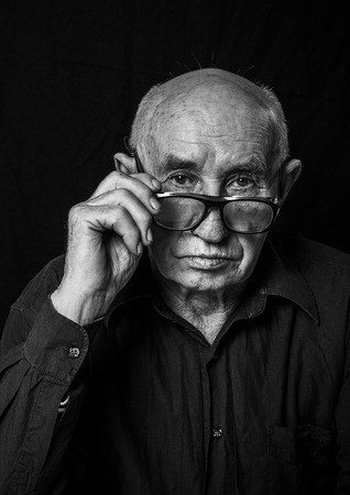 Black and White Portrait of an elderly man with a serious expression. photo
