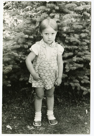 USSR - CIRCA 1986: An antique photo shows little girl standing under the tree