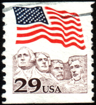 UNITED STATES OF AMERICA - CIRCA 1991: A stamp printed in the USA shows American flag waving proudly above Mt. Rushmore, circa 1991