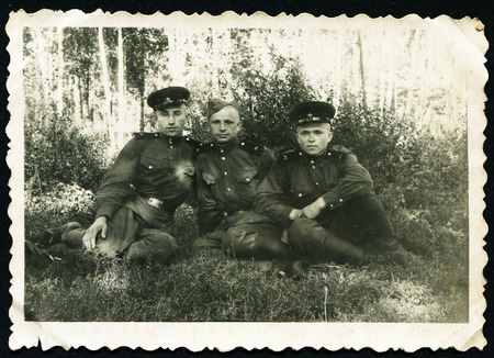 USSR - CIRCA 1953: Postcard shows three soldiers sitting under a tree, of the USSR, 1953