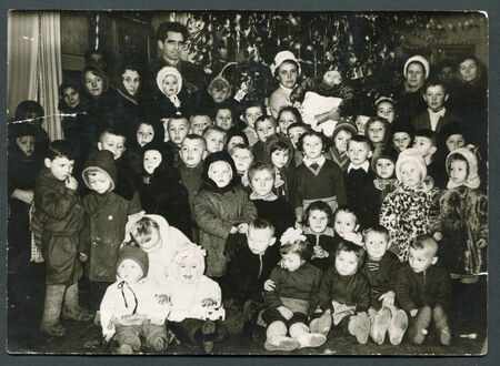 USSR - CIRCA 1950s: An antique photo shows a group of children under the Christmas tree