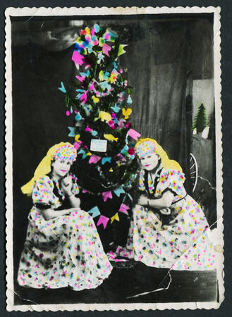 USSR - CIRCA 1940s: An antique photo shows Two girls in suits sitting around the Christmas tree