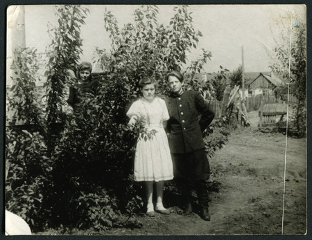 USSR - CIRCA 1960s: An antique photo shows  two women and a man standing near the apple tree in the garden , circa 1960s