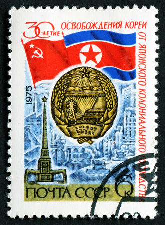 RUSSIA - CIRCA 1975: stamp printed by Russia, shows Flags of USSR, North Korea, arms of N. K., Liberation monument, Pyongyang, circa 1975