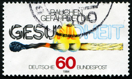 GERMANY - CIRCA 1984: A stamp printed in Germany shows burning match and the inscription Smoke endangers the health, circa 1984