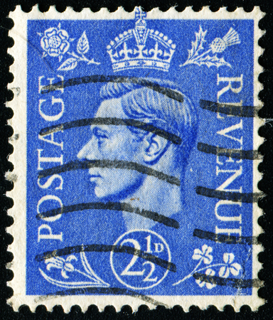 UNITED KINGDOM - CIRCA 1950 to 1952: An English One and a Half Pence Green Used Postage Stamp showing Portrait of King George VI, circa 1950 to 1952