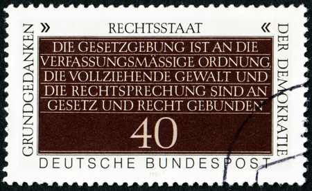 interchangeably: GERMANY - CIRCA 1981: A stamp printed in German Federal Republic showstext - separation of powers, often imprecisely used interchangeably with the trias politica principle, circa 1981 Editorial