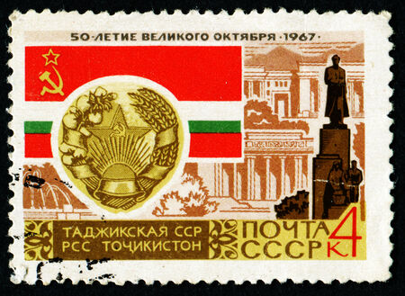 """USSR - CIRCA 1967: A stamp printed in the USSR, shows Arms and Flag of USSR republic with the inscription """"Tajik SSR"""" from the series 50th Anniversary of Great October, circa 1967"""
