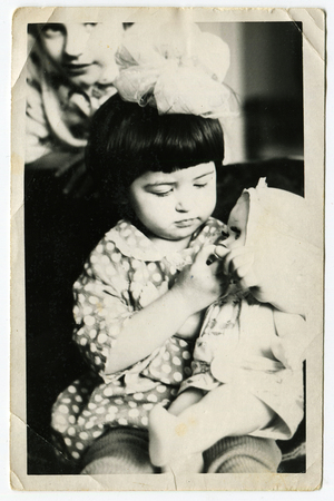 studio b: USSR - CIRCA 1965: An antique photo shows little girl with a doll Editorial