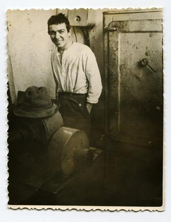 Ussr - CIRCA 1980s: An antique Black & White photo show a young man near the machine