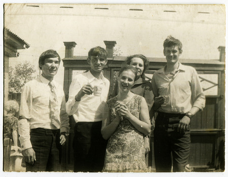 black and white photograph: Ussr - CIRCA 1960s: An antique Black & White photo show youth drinking tea on the street Editorial