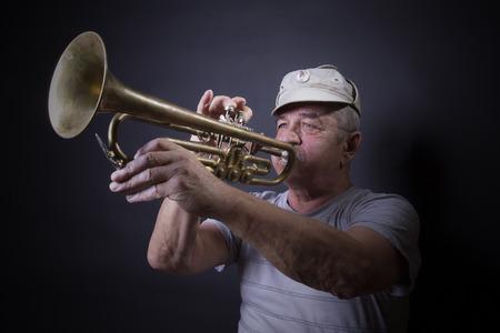 trombon: hombre maduro posando con tromb�n en frente del retrato tel�n de fondo  Foto de archivo
