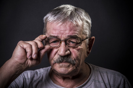 corrects: old man corrects glasses Stock Photo