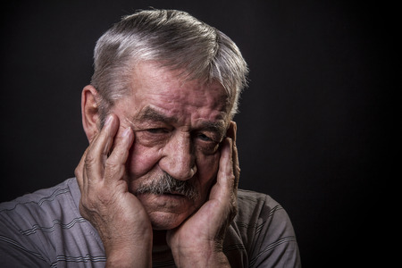 tense: portrait of an old gray-haired man with a mustache