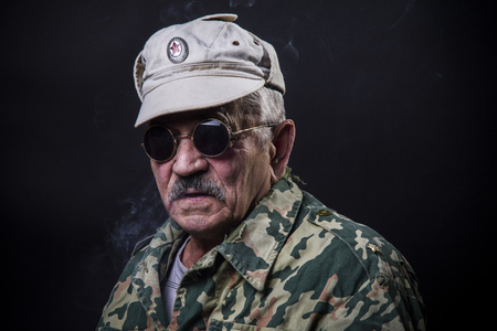 grumpy old man: old man in sunglasses and camouflage Stock Photo