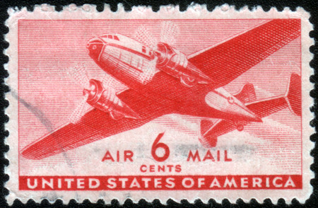 ephemera: USA - CA. 1943: United States postage stamp in the value of 6 cents used for overseas air mail deliveries showing a vintage transport plane in mid-air and the print Air Mail