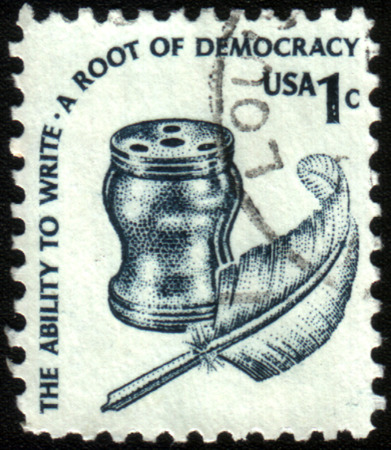 ink pot: USA - CIRCA 1975: a definitive stamp printed in the United States shows a quill pen (feather) and an ink pot. The ability to write. A root of democracy. Scott catalog A984, circa 1975