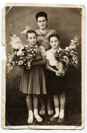 USSR - 1970s: An antique photo shows mother and two daughters schoolgirl with bouquets of flowers