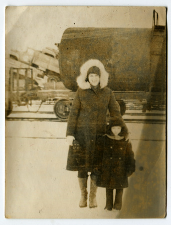 circa: USSR - CIRCA 1960s: An antique photo shows Mother and daughter outdoors in winter, USSR, circa 1960s