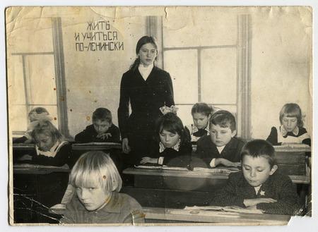 """URSS - alrededor de 1970: Una foto antigua muestra el profesor y los estudiantes, la escritura en la pared """"para aprender a vivir en el leninista"""", URSS, en torno a 1970 Foto de archivo - 49676637"""