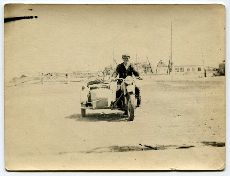 the ussr: USSR - CIRCA 1980s: An antique photo shows men on a motorcycle, USSR, circa 1980s