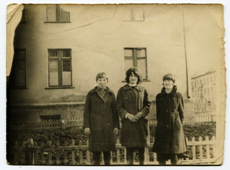 Ussr - CIRCA 1970s: An antique Black & White photo show Three girls on the background of the house 新聞圖片