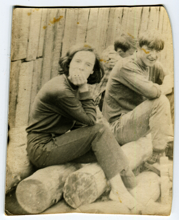 Ussr - CIRCA 1970s: An antique Black & White photo show young men sit on logs in the yard