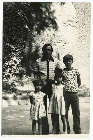 Ussr - CIRCA 1970s: An antique Black & White photo show father of three children 新聞圖片