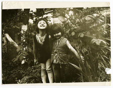 Ussr - CIRCA 1970s: An antique Black & White photo show two little beautiful girls in the garden 新聞圖片