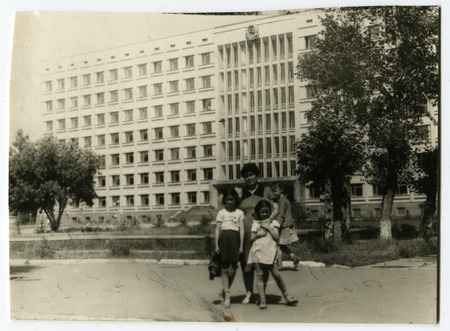 Ussr - CIRCA 1970s: An antique Black & White photo show Mother with children on the background of the hotel Kyzyl Zhar