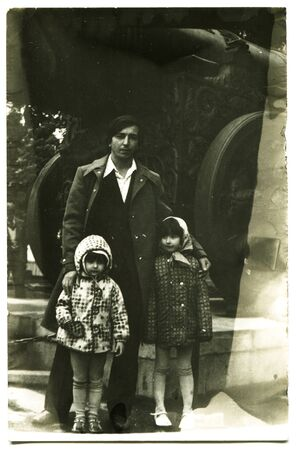 Ussr - CIRCA 1970s: An antique Black & White photo show father and three children near the King cannon