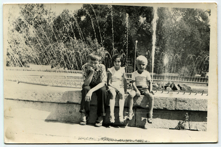generational: Ussr - CIRCA 1970s: An antique Black & White photo show three children on the fountain in the park