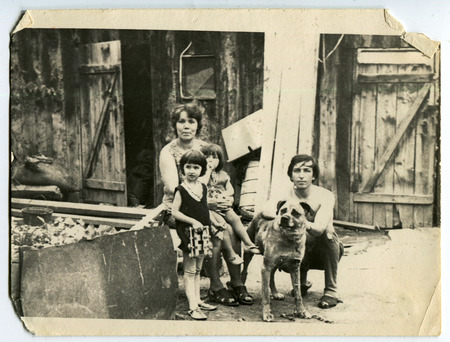 Ussr - CIRCA 1970s: An antique Black & White photo show Family photo with children and a dog in the yard