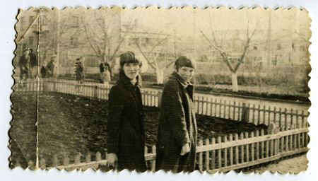 Ussr - CIRCA 1970s: An antique Black & White photo show two women walking on a city along the fence