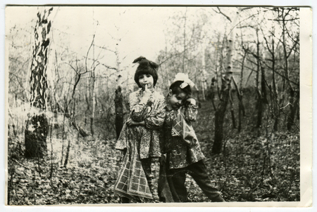 Ussr - CIRCA 1970s: An antique Black & White photo show Two girls play in the woods