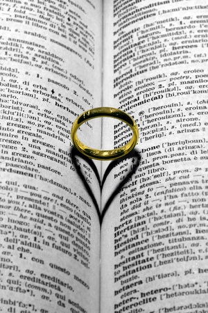 a gold wedding ring on pages of book photo