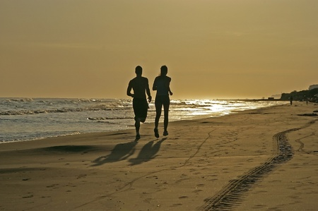 man and woman running on the beach Stock Photo