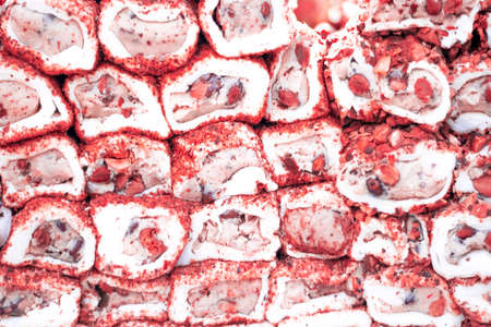 Turkish delight lined up on the workbench. White and red colors. There's peanuts, nuts, walnuts.