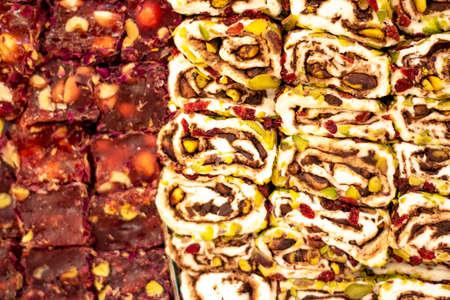 Turkish Delight aufgereiht auf der Werkbank. Weiße und rote Farben. Es gibt Erdnüsse, Nüsse, Walnüsse.