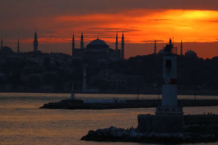 View of Hagia Sophia over the sea. Sunset. Gold color sky. Lighthouse