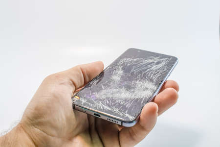 Broken glass mobile phone. It stands in your hand. White background. Stockfoto