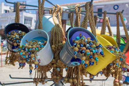 Decorative colorful small buckets sold in the store. Yellow color hanging with ropes. There are evil eye beads inside.