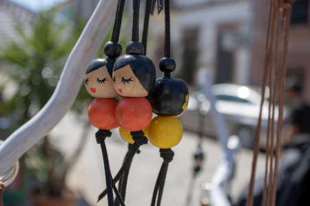 Keychains made of wooden beads. On the beads is a picture of a slanted lady in the Asian region.