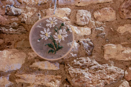 Picture of small flour sieve hanging on wall and knitted daisy on sieve. Brick wall. Banque d'images - 133063240