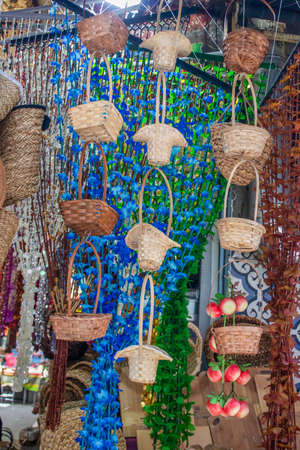 Small decorative baskets hanging in front of the store. Draperies used for home decoration in the background.