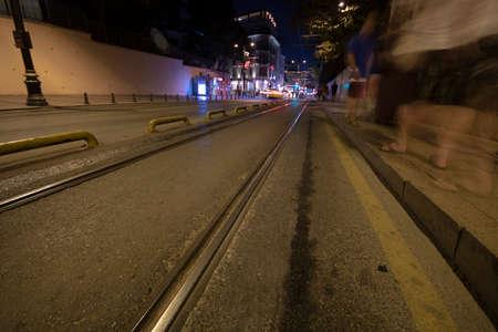 Rieles de tranvía sobre asfalto. Gente caminando y semáforos en la acera. Filmado de noche con larga exposición.