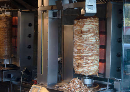 Hühnchen- und Fleisch-Döner-Nahaufnahme. Rotierende Maschine Nahaufnahme. Fleisch schneiden. Standard-Bild