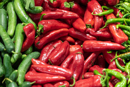 Vegetables on greengrocer counter. Red and green chillies close-up. Used in vegetable dishes.