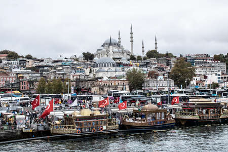 Istanbul, Turkey - October-5.2019: Eminonu Square is a very old square. It is crowded around the clock. Grilled fish are sold in historic boats. Фото со стока - 137711141