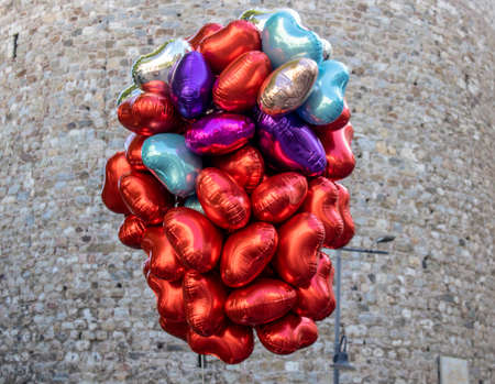 Close-up of a different color and assorted balloons of balloon vendor. Historical stone wall in background. The photo was taken in front of the Galata Tower.